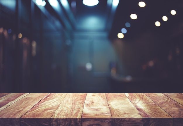 Holztischplatte auf unscharfem gegencaféladen mit glühbirnenhintergrund