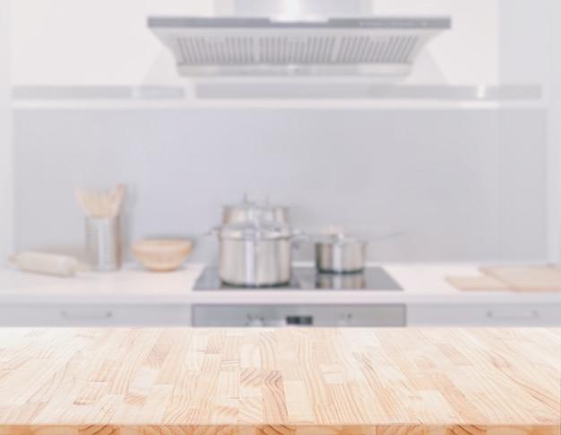 Holztischplatte auf unscharfem küchenraumhintergrund. kann zur anzeige oder montage ihrer produkte verwendet werden.