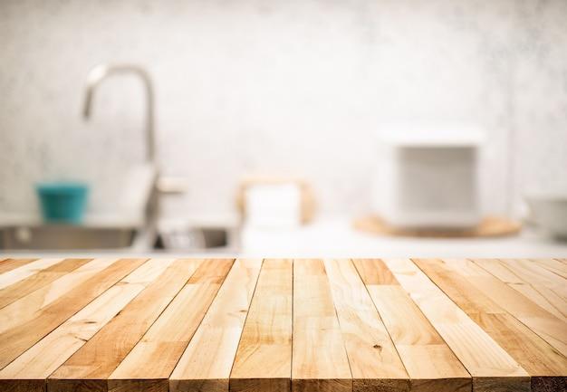 Holztischplatte auf unscharfem küchentheken- (raum-) hintergrund. für montageproduktanzeige oder entwurfsschlüssel visuelles layout.