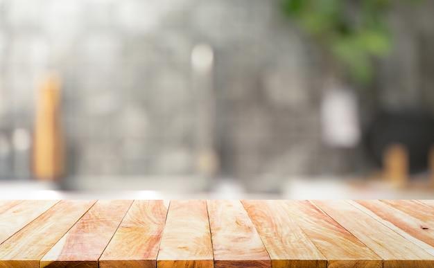 Holztischplatte auf unscharfem küchenthekenhintergrund. für montageproduktanzeige oder entwurfsschlüssel visuelles layout.