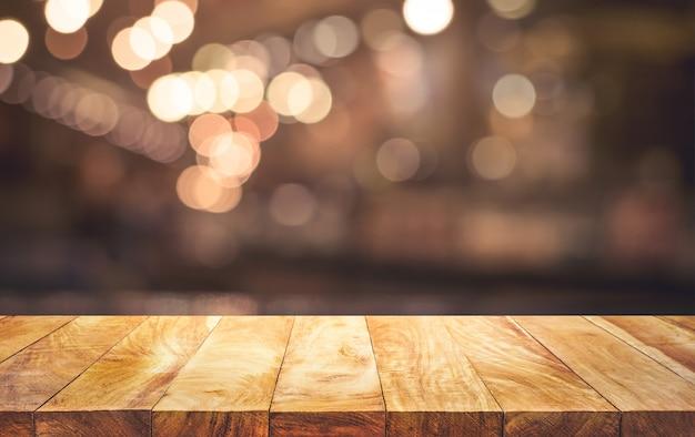 Holztischplatte (bar) mit unscharfem hellem bokeh im dunklen nachtcafé, restauranthintergrund. keine leute