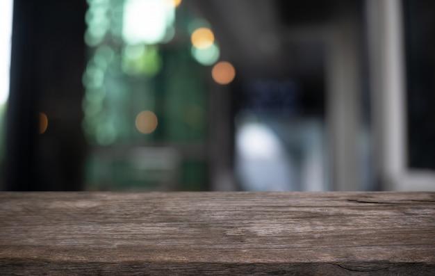 Holztischplatte im innenraum des unscharfen hintergrundraums
