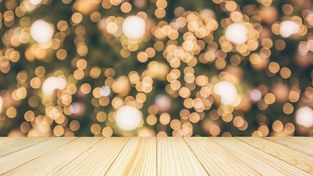 Holztischplatte mit abstraktem weihnachtsfeiertag festliches bokeh-licht auf baum unscharfem hintergrund für montageproduktanzeige
