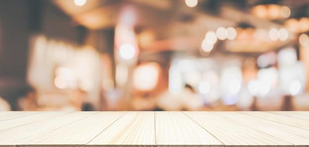 Holztischplatte mit restaurantcafé oder kaffeehausinnenraum mit abstraktem unscharfem unschärfehintergrund der leute