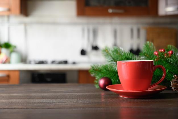 Holztischplatte mit roter tasse kaffee und verschwommener weihnachtsküche.