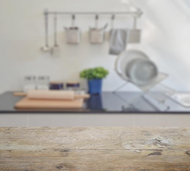 Holztischplatte mit unschärfe des modernen keramischen küchengeschirrs und der geräte auf der arbeitsplatte