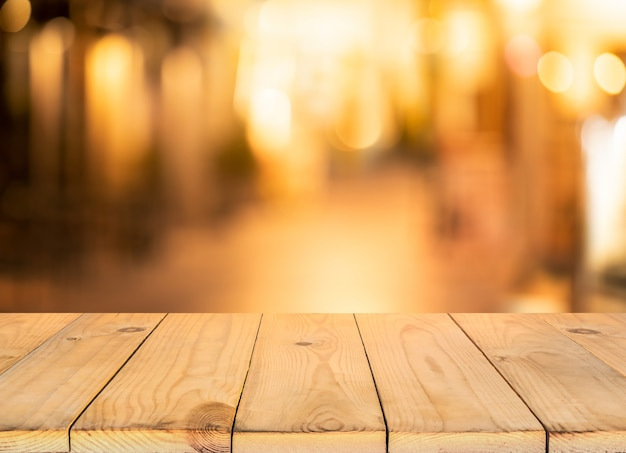 Holztischplatte mit verschwommenem hellem bokeh im dunklen nachtcafé