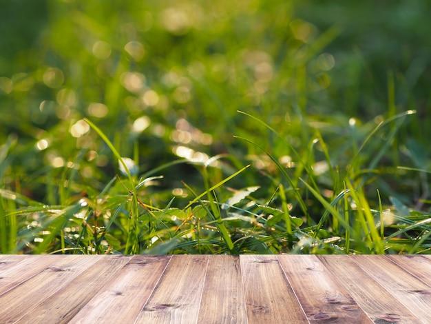 Holztischplatte über grünem feld mit sonnenlicht