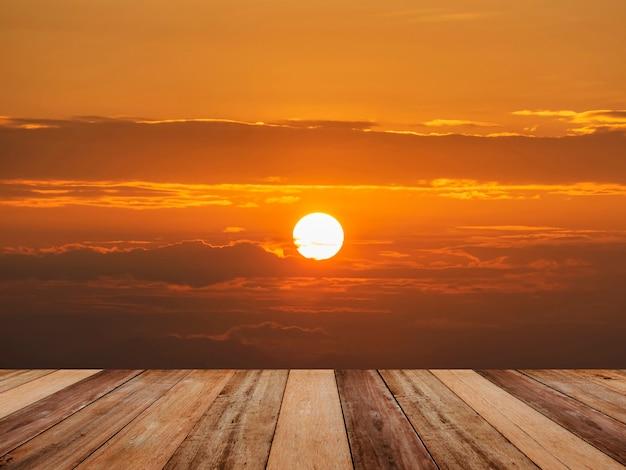 Holztischplatte über heller sonne und dramatischem sonnenaufgangwolkenhimmel.