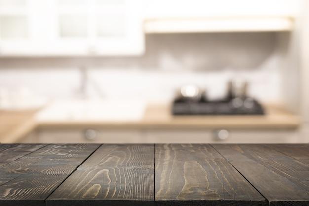 Holztischplatte und moderne defokussierte küche zur präsentation ihrer produkte. unscharfer abstrakter küchenhintergrund.