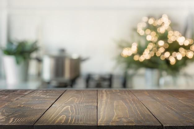 Holztischplatte und verschwommene küche verzierten weihnachtsbaum.