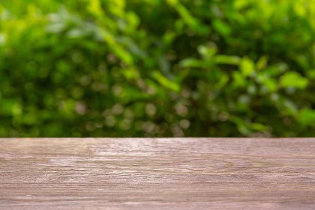 Holztischplatten gegen hintergrund der blätter. platzierung ihres produktes