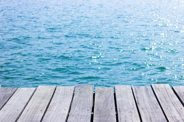 Holztischspitze mit blauem seehintergrund.