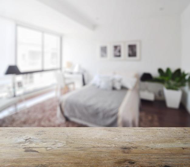 Holztischspitze mit unschärfe des modernen schlafzimmerinnenraums als hintergrund