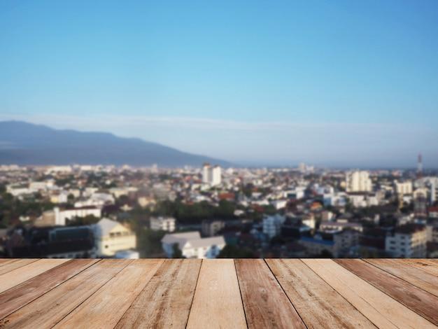 Holztischspitze über unschärfehintergrund des stadtbilds und des berges morgens.