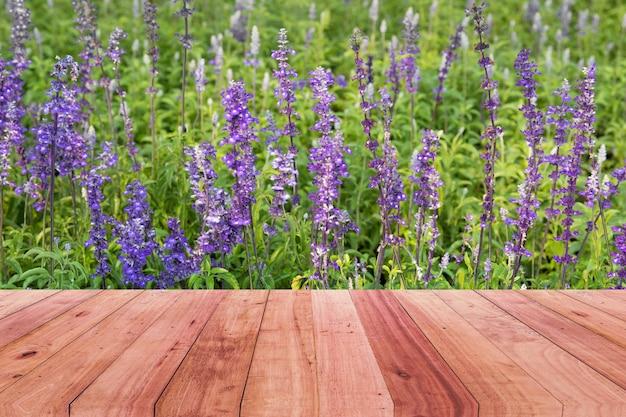 Holztischspitze und purpurroter blumenhintergrund