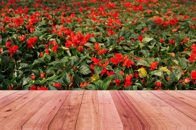 Holztischspitze und roter blumenhintergrund