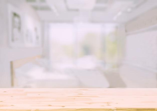 Holztischspitze vor unscharfem schlafzimmerinnenhintergrund