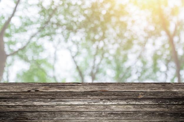 Holztischvordergrund mit grünem hintergrund der unschärfe waldfür anzeigenaturprodukte