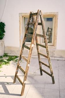 Holztreppe steht auf einer fliese im hof des hauses