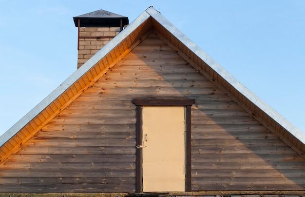 Holztür am eingang zum dachboden auf der straße, nahaufnahme eines teils eines alten gebäudes