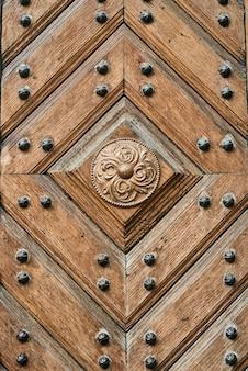 Holztür mit metallnieten. antikes retro-plankenmuster mit metalleinsätzen