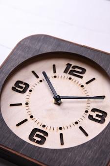 Holzuhr gemacht in der hand auf hölzernem hintergrund. nahansicht. platz für einen text.