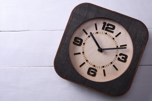Holzuhr gemacht in der hand auf hölzernem hintergrund. nahansicht. platz für text.