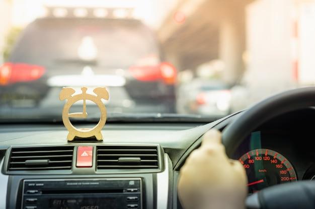 Holzuhr modell auf der konsole vor dem auto, das im verkehr stecken