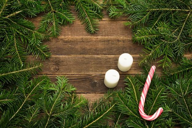 Holzuntergrund. tannenzweige, süßigkeiten und kerzen. weihnachtskonzept