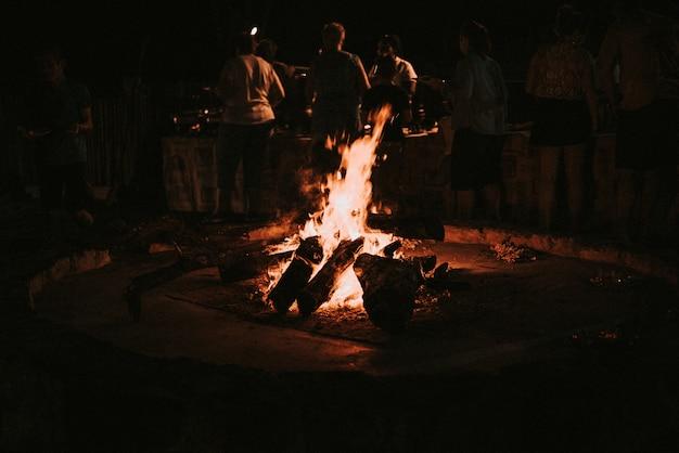 Holzverbrennung in einem nächtlichen lagerfeuer menschen