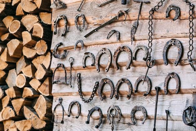 Holzwand mit altem rostigem hufeisen-brennholzstapel