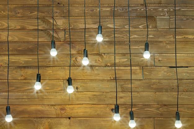 Holzwand mit glühbirne. natürliches gealtertes brett an der wand im raum. wand mit leuchtenden glühbirnen verziert.