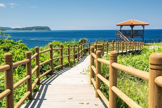 Holzweg, der zu einem aussichtspunkt führt, um die wunderschöne seelandschaft mit ihrem blauen meer zu betrachten. iriomote island.