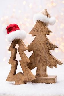 Holzweihnachtsbaum mit weihnachtsmannmütze.