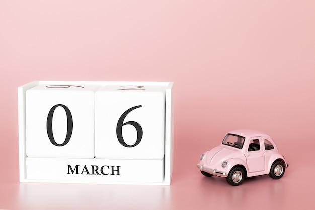 Holzwürfel 6. märz. tag 6 des märzmonats, kalender auf einem rosa hintergrund mit retro- auto.