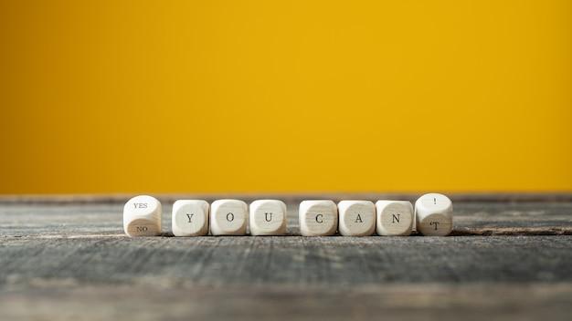 Holzwürfel drehen sich, um ein ja zu buchstabieren. sie können ein konzeptionelles bild unterschreiben. über gelbem hintergrund mit kopierraum.
