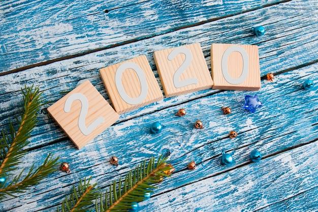 Holzwürfel für ihre neujahrsdaten draufsicht neujahrskonzept blauer hölzerner hintergrundtannenzweig