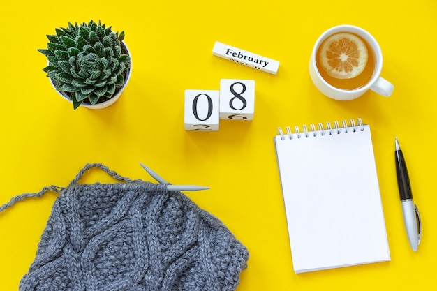 Holzwürfel kalender 8. februar. tasse tee mit zitrone, leeren offenen notizblock für text. topf mit saftigem und grauem stoff t