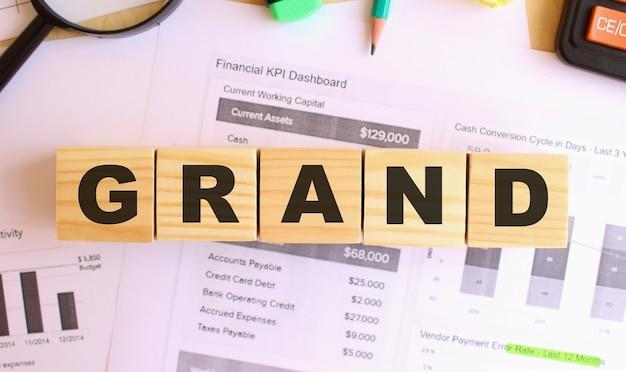 Holzwürfel mit buchstaben auf dem tisch im büro. text grand. finanzkonzept.
