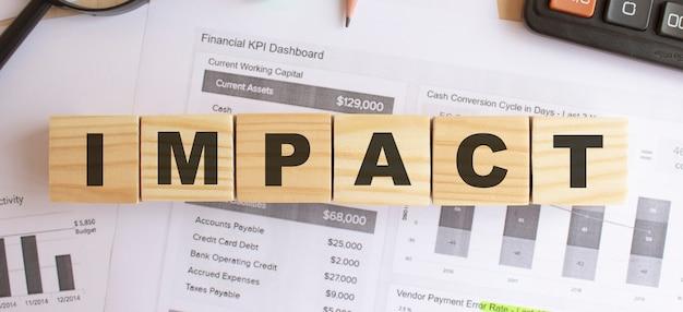 Holzwürfel mit buchstaben auf dem tisch im büro. text impact. finanzkonzept.