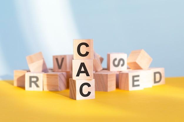 Holzwürfel mit buchstaben cac in einer vertikalen pyramide angeordnet, grauer und gelber hintergrund, geschäftskonzept. cac - kurz für kundenakquisitionskosten