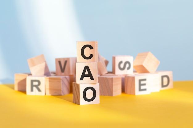 Holzwürfel mit buchstaben cao angeordnet in einer vertikalen pyramide, grauem und gelbem hintergrund, geschäftskonzept. cao - abkürzung für chief accounting officer