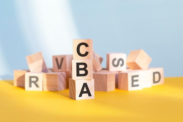 Holzwürfel mit buchstaben cba in einer vertikalen pyramide angeordnet, grauer und gelber hintergrund, geschäftskonzept. cba – kurz für kosten-nutzen-analyse