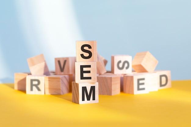 Holzwürfel mit buchstaben sem in einer vertikalen pyramide angeordnet, gelber hintergrund, reflexion von der tischoberfläche, geschäftskonzept. sem – kurz für suchmaschinenmarketing