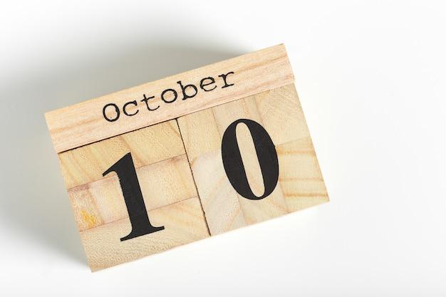 Holzwürfel mit datum auf weißem hintergrund. 10. oktober