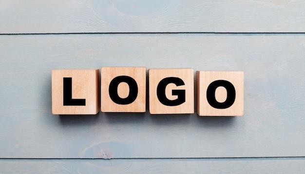 Holzwürfel mit dem text logo auf einer hellblauen holzoberfläche
