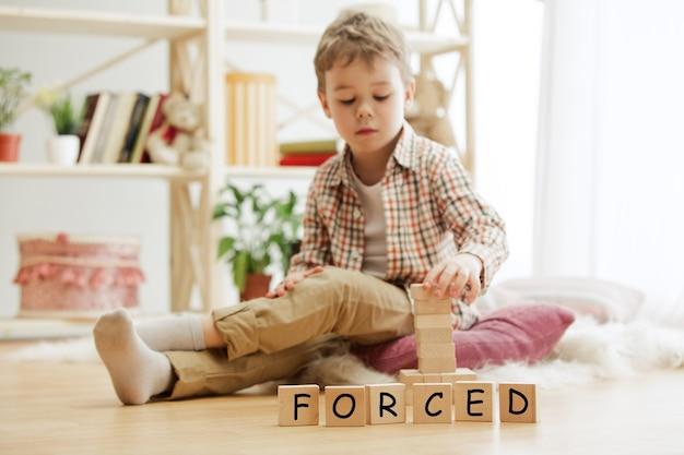 Holzwürfel mit dem wort gezwungen in den händen des kleinen jungen zu hause. konzeptbild über bildung, kindheit und soziale probleme.