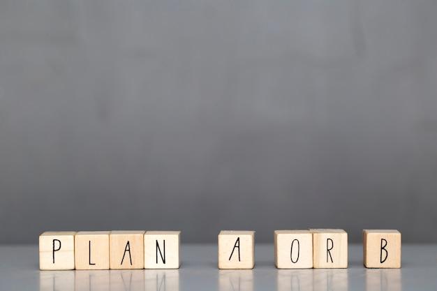 Holzwürfel mit dem wort plan a oder b auf grauem hintergrund, geschäftskonzept
