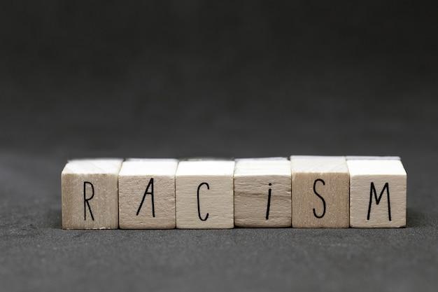 Holzwürfel mit dem wort rassismus auf dunklem hintergrund, konzept der schwarzen lebensmaterie